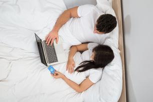 Couple Lying On Bed Shopping Onlineの写真素材 [FYI00661095]