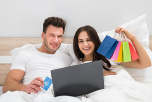 Colorful Shopping Bags With Couple Lying On Bedの写真素材 [FYI00661096]