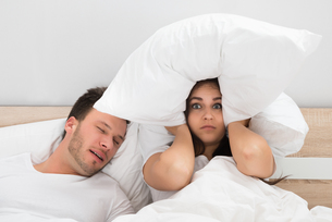 Woman Covering Ears While Man Snoring On Bed At Homeの写真素材 [FYI00661098]