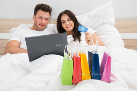 Colorful Shopping Bags With Couple Lying On Bedの写真素材 [FYI00661099]