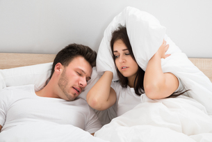 Woman Covering Ears While Man Snoring On Bed At Homeの写真素材 [FYI00661102]