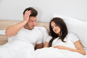Man Looking At Woman Snoring In Bedの写真素材 [FYI00661103]