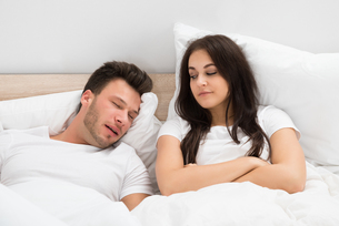 Woman Looking At Man Snoring In Bed At Homeの写真素材 [FYI00661104]