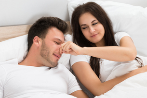 Woman Holding Husband's Nose While Sleepingの写真素材 [FYI00661109]