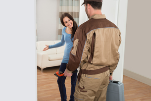 Happy Woman Welcoming Plumber At Homeの写真素材 [FYI00661127]