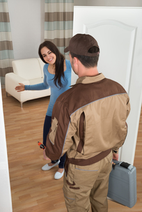 Happy Woman Welcoming Plumber At Homeの写真素材 [FYI00661134]
