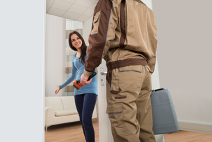 Happy Woman Welcoming Plumber At Homeの写真素材 [FYI00661137]