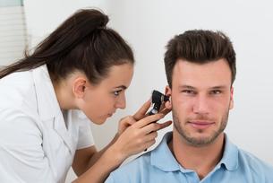 Doctor Examining Man's Earの写真素材 [FYI00661143]