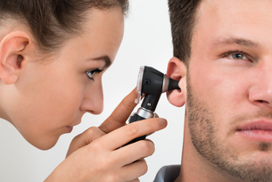 Doctor Examining Man's Earの写真素材 [FYI00661146]