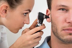 Doctor Examining Man's Earの写真素材 [FYI00661147]