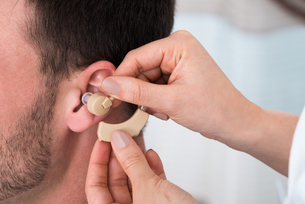 Hands Inserting A Hearing Aid Into A Man's Earの写真素材 [FYI00661150]