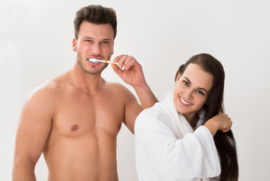 Shirtless Man Brushing His Teeth And Her Wife Combing Hairの写真素材 [FYI00661158]