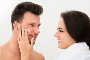 Woman Applying Moisturizer On Man's Cheekの写真素材 [FYI00661160]