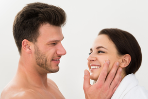 Man Applying Moisturizer On Woman's Cheekの写真素材 [FYI00661164]