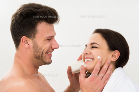 Man Applying Moisturizer On Woman's Cheekの写真素材 [FYI00661171]