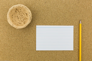 ceramic nest on cork board with paper and pencilsの素材 [FYI00661441]