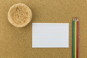 ceramic nest on cork board with paper and pencilsの素材 [FYI00661442]