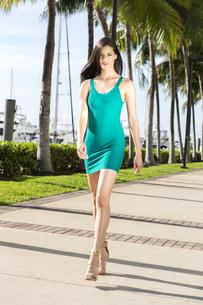Young hispanic woman walking, outdoors. Marina with palm trees.の写真素材 [FYI00661822]