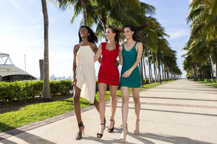Three women walking, on a warm sunny summer day. Marina with palm trees.?の写真素材 [FYI00661825]