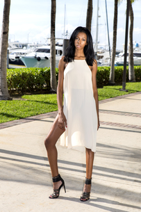 Young african american woman walking, outdoors. Marina with palm trees.の写真素材 [FYI00661830]