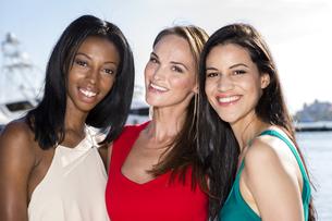 Three women posing in marina harbor, yachts on background.の写真素材 [FYI00661832]