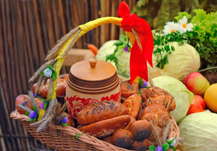 Basket of bread, decorated with ribbons, and vegetablesの写真素材 [FYI00662070]