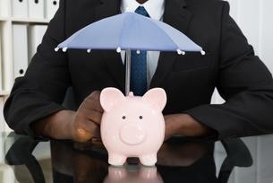 Businessman With Piggybank And Umbrellaの写真素材 [FYI00662189]