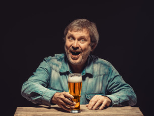 The smiling man in denim shirt with glass of beerの写真素材 [FYI00662207]