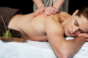 Lying man getting a back massageの写真素材 [FYI00662297]