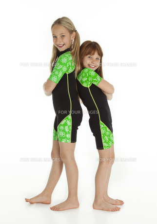 Two Little Girls Standing Back to Back Wearing Wetsuitsの写真素材 [FYI00662406]