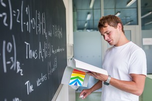 Handsome college student solving a math problem during math class in front of the blackboard/chalkboard (color toned image)の写真素材 [FYI00662436]