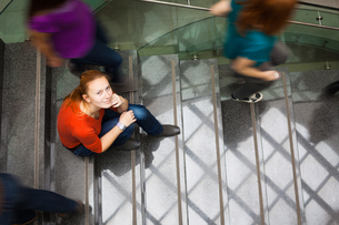 At the university/college - Students rushing up and down a busy stairway - confident pretty young female student looking upwards while listening to music on her mp3 player (color toned image)の写真素材 [FYI00662439]