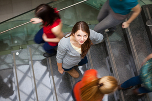 At the university/college - Students rushing up and down a busy stairway - confident pretty young female student looking upwards while listening to music on her mp3 player (color toned image)の写真素材 [FYI00662441]