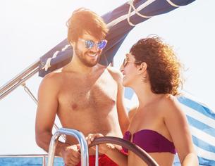 Cheerful couple driving sailboatの写真素材 [FYI00662617]