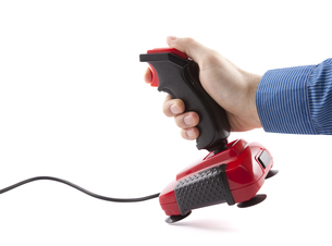 Computer joystick with hand isolated on white. Clipping path included.の写真素材 [FYI00662675]
