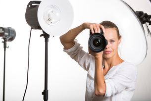 Pretty, female pro photographer with digital camera - DSLR and a huge telephoto lens in her well equiped studio, taking photos (color toned image  shallow DOF)の写真素材 [FYI00662714]