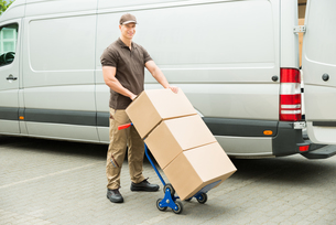 Delivery Man Holding Trolley With Cardboard Boxesの写真素材 [FYI00662766]