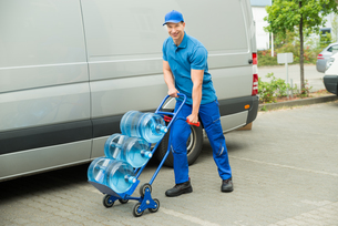 Delivery Man Holding Trolley With Water Bottlesの写真素材 [FYI00662768]