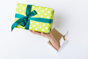 Hand break through paper with green present boxの写真素材 [FYI00662873]
