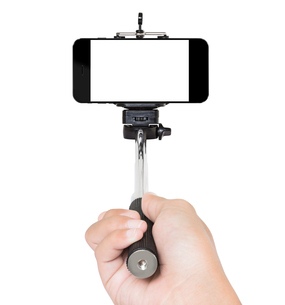 hand using selfie stick isolated white clipping path insideの写真素材 [FYI00662921]