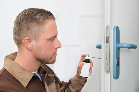 Male Carpenter Lubricating Doorの写真素材 [FYI00662934]