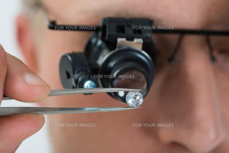 Person Looking At Diamond With Magnifying Loupeの写真素材 [FYI00662937]