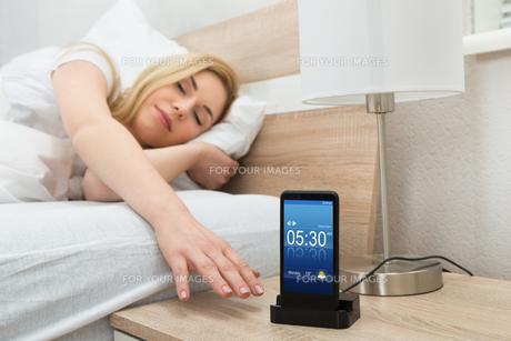 Woman Snoozing Alarm On Mobile Phone Screenの写真素材 [FYI00662939]