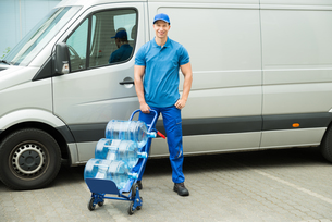 Delivery Man Holding Trolley With Water Bottlesの写真素材 [FYI00662941]
