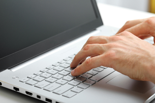 hands typing on laptop keyboardの写真素材 [FYI00663005]