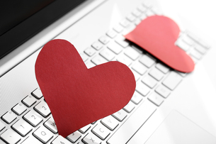 internet dating concept - two paper hearts on computer keyboardの写真素材 [FYI00663006]