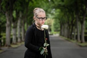 M?dchen mit wei?er Rose trauert auf Friedhofの素材 [FYI00663070]