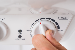 Person Turning The Knob Of Electric Boilerの写真素材 [FYI00663165]