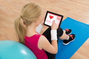 Woman Looking At Heart Pulse Rate On Digital Tabletの写真素材 [FYI00663171]