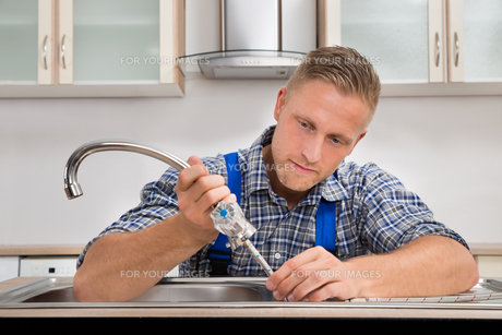 Plumber Fixing Faucet In Sinkの写真素材 [FYI00663176]